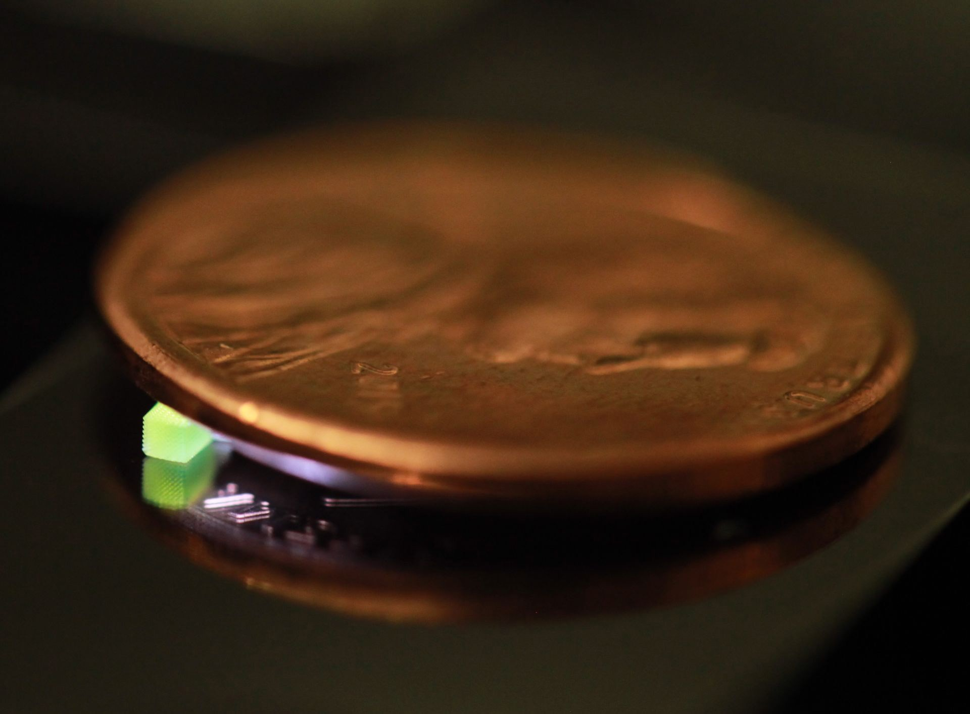 A millimeter-scale structure with submicron features is supported on a U.S. penny on top of a reflective surface