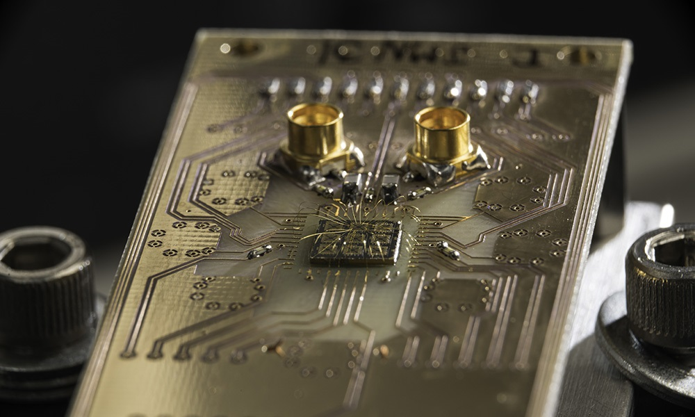 A quantum processor semiconductor chip is shown connected to a circuit board