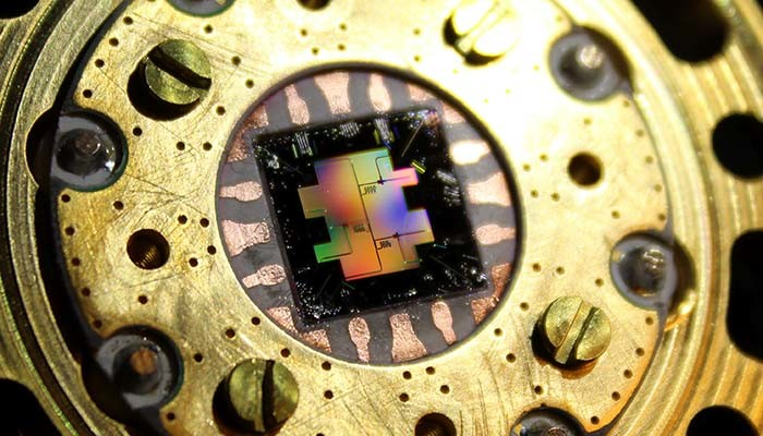 Photo of the centimeter-sized silicon chip which has three separate superconducting quantum bits