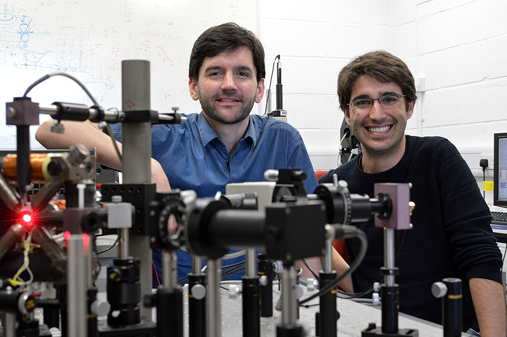 Amalio Fernández-Pacheco, principal investigator of the project (left) and Dédalo Sanz-Hernández, lead autor of the work (right) posing with the optical system used at the University of Cambridge to read information from 3D magnetic nanostructures