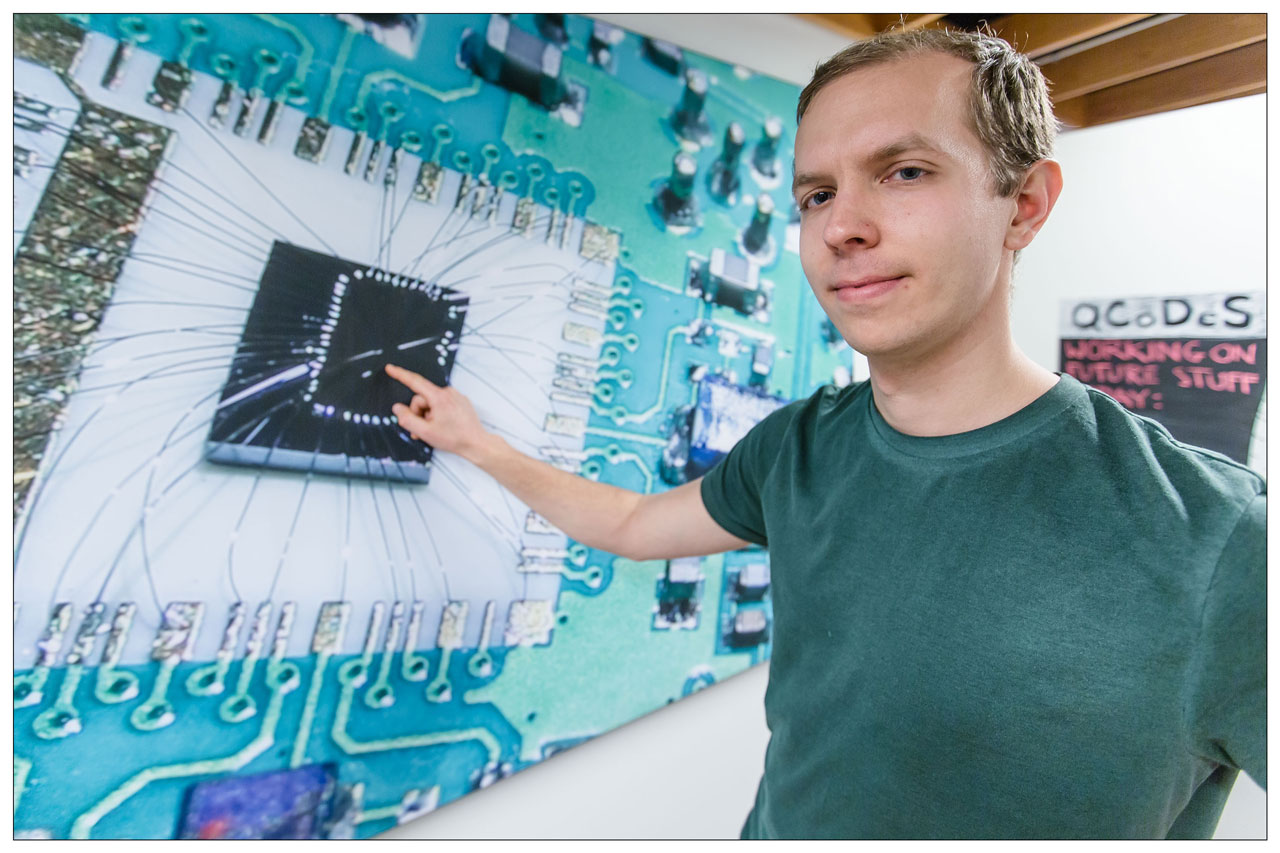 Filip Malinowski – pointing at a chip similar to the one which the NBI-scientists used in their experiments in order to put qubits into reverse.
