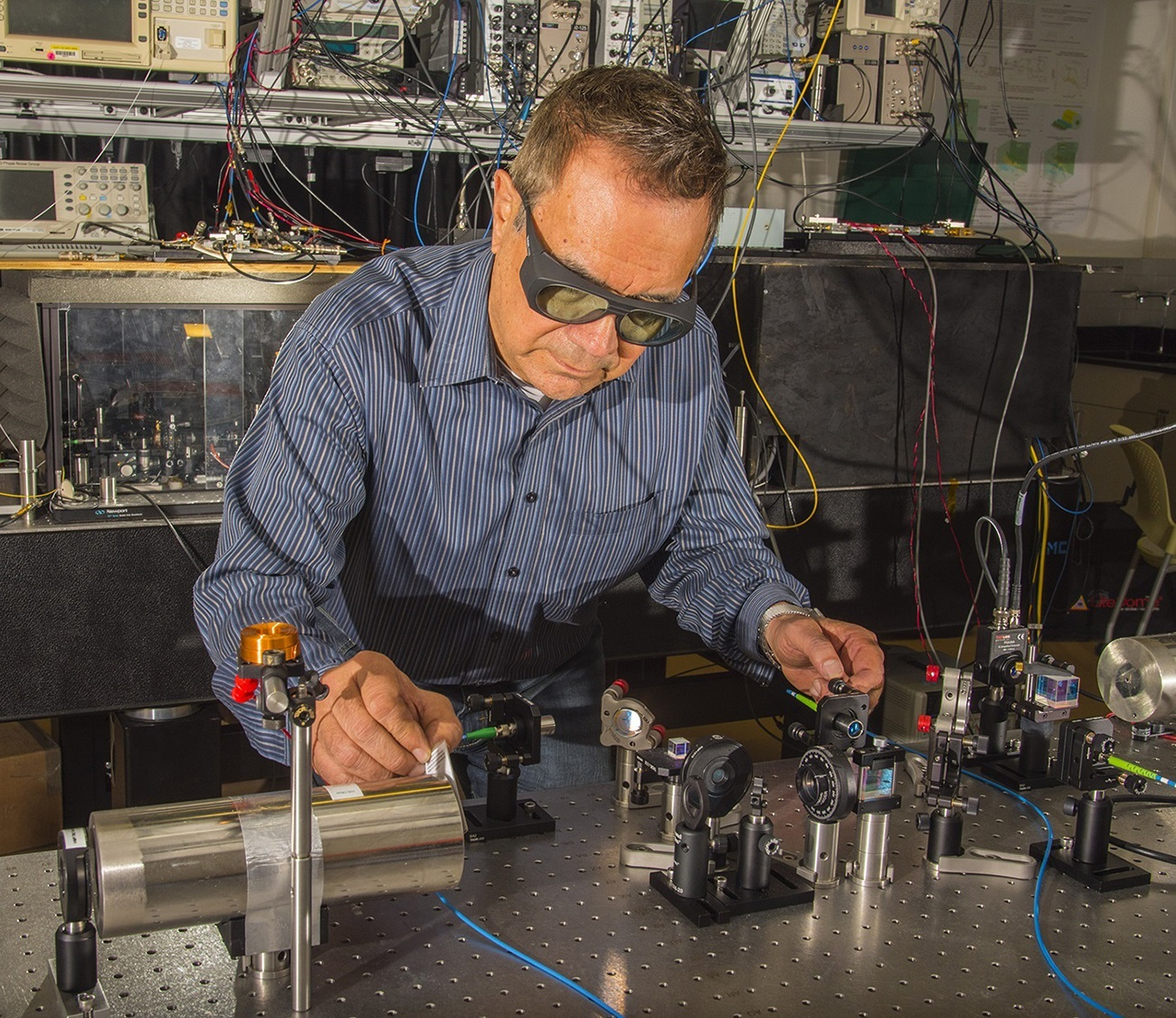 NIST physicist Dave Howe aligns a laser beam to pass through a tiny glass cell of rubidium atoms inside the cylindrical magnetic shield